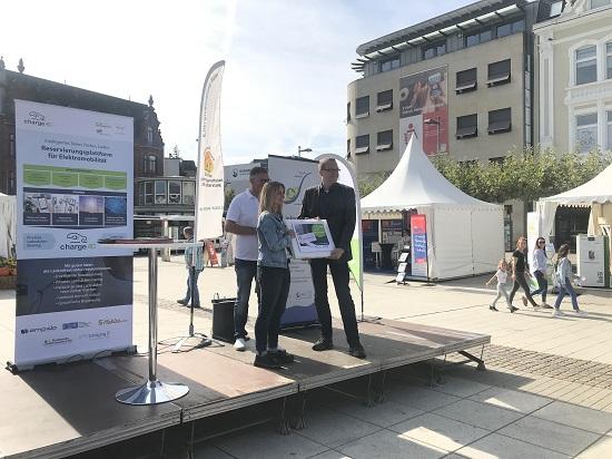 Übergabe des Durchstartersets durch Dominique Sévin an Claudia Beck (Kreisbeigeordnete) und Ralf Rupp (Klimaschutzmanager)